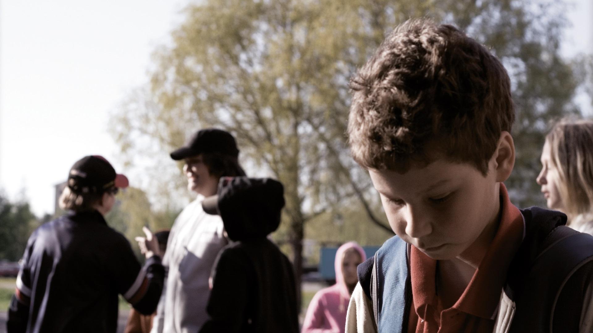 Kuvituskuva alakoulainen poika alakuloisena kun hänet on jätetty porukan ulkopuolelle