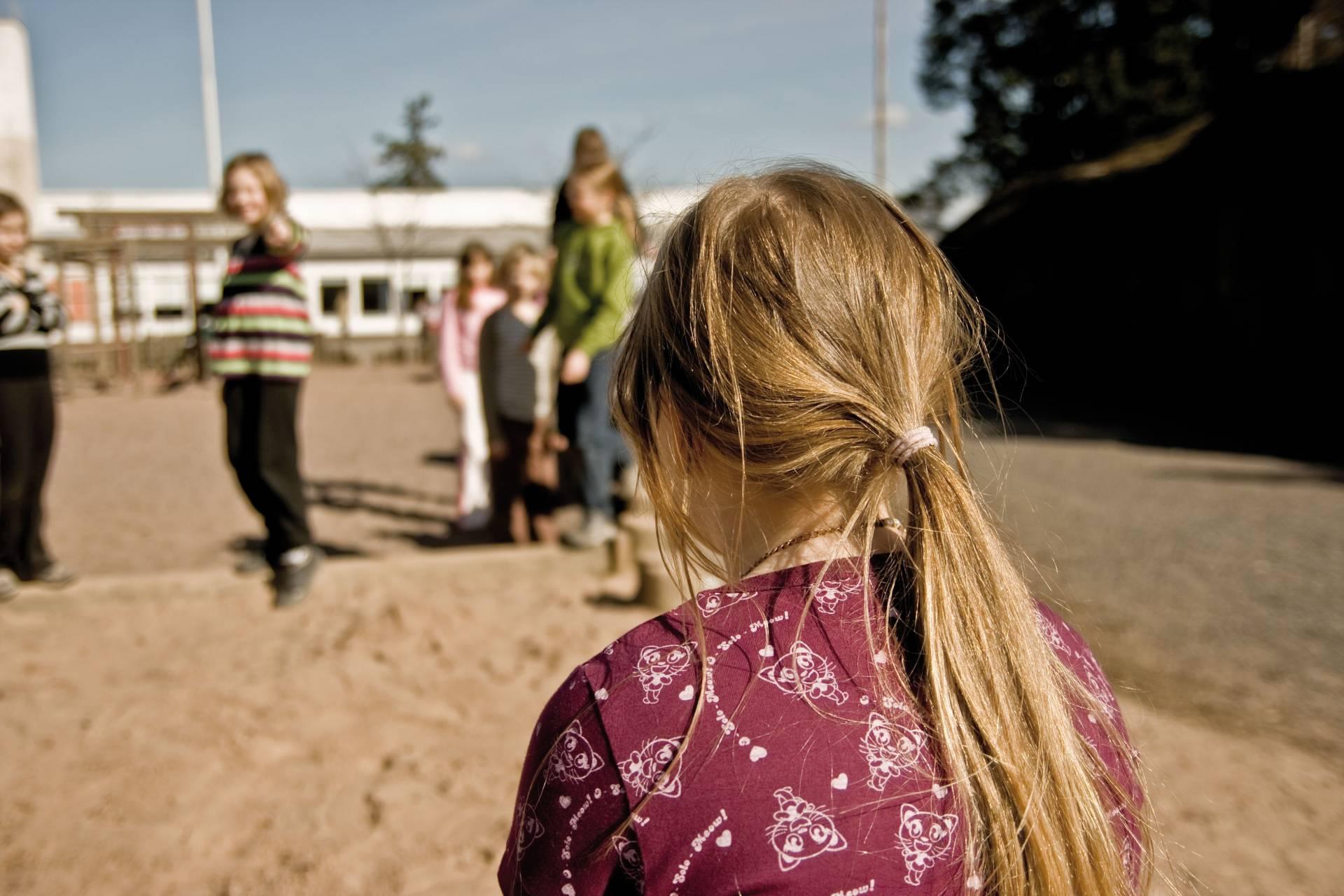 Kuvituskuva tytöstä joka jäänyt leikin ulkopuolelle koulun pihalla